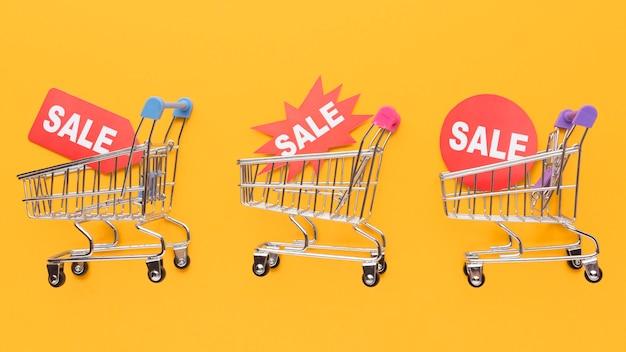 Carrelli della spesa che tengono le etichette di vendita
