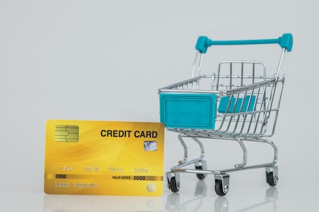 Carrelli della spesa con la carta di credito gialla, e-commerce acquisti online.