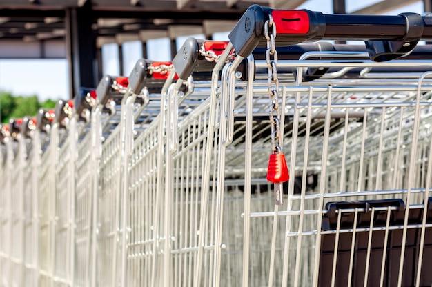 Carrelli della spesa nel negozio, assemblati in fila nel parcheggio. avvicinamento.