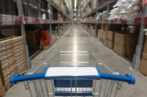Carrello blu con la vista vaga dell'interno del magazzino con il prodotto sugli scaffali nel fondo del centro del centro commerciale del grande magazzino