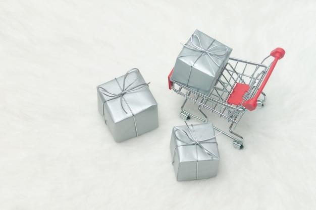 Carrello con i contenitori di regalo su fondo bianco