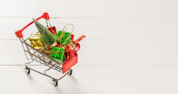 Carrello con l'albero di natale e contenitori di regalo miniatura su legno bianco