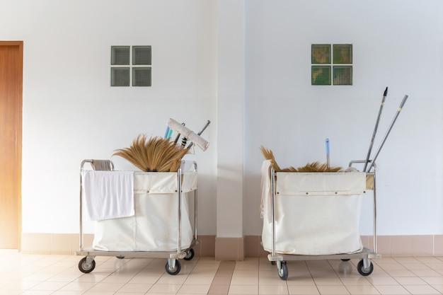 Carrello dei pulitori con le attrezzature di pulizia all'hotel con il fondo della parete