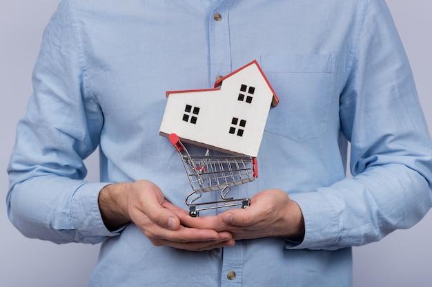 Carrello del giocattolo della tenuta dell'uomo e casa di modello. casa d'acquisto sul concetto di credito