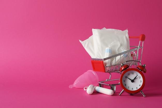 Carrello del negozio con accessori per il periodo mestruale sulla superficie rosa