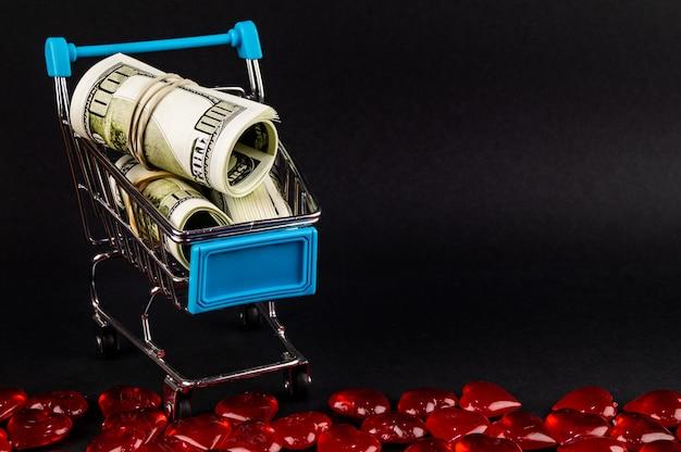 Carrello del supermercato con soldi dentro su oscurità