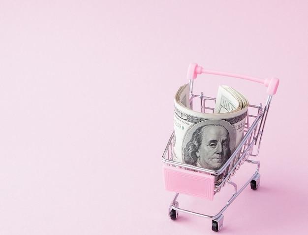 Carrello del supermercato pieno di banconote in dollari usa. libero scambio. mercato monetario. stile minimalista. carrello del negozio al supermercato. vendita, sconto