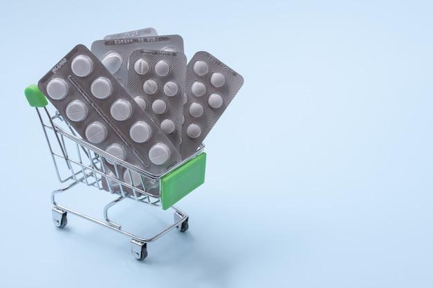 Carrello della spesa con le pillole, concetto di acquisto della farmacia. pillole nel carretto della spesa
