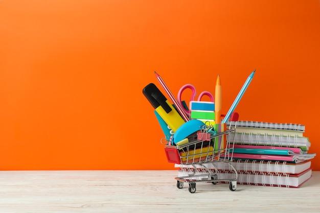 Carrello della spesa con materiale scolastico, spazio per il testo