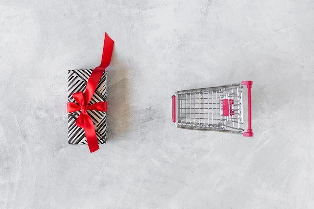 Carrello della spesa con scatola regalo sul tavolo