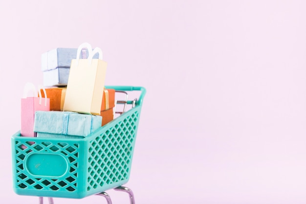 Carrello della spesa con scatole regalo colorate e borse della spesa