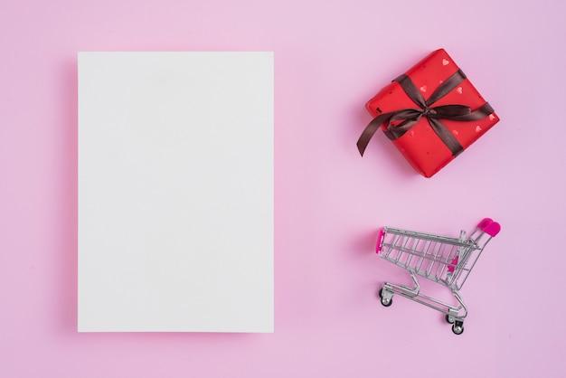 Carrello della spesa e regalo vicino al foglio di carta
