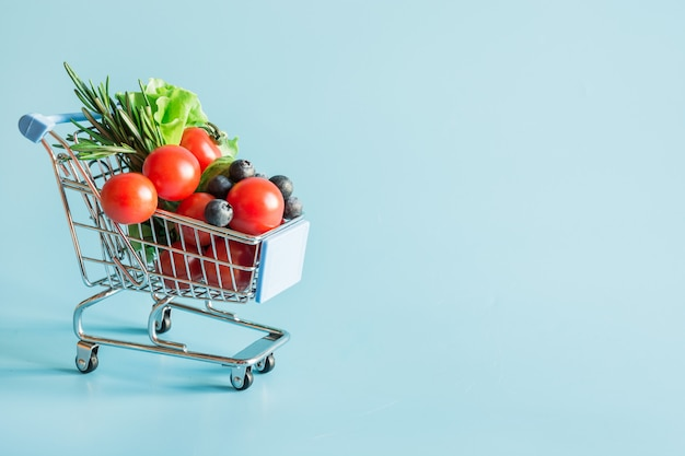 Carrello della spesa pieno di generi alimentari di verdure fresche