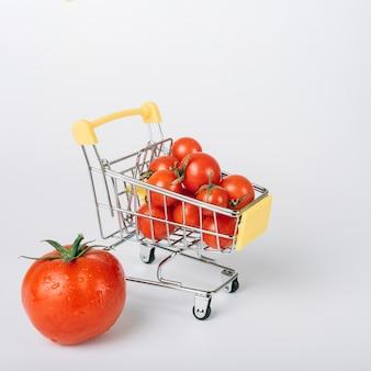 Carrello della spesa pieno di pomodori rossi freschi su sfondo bianco