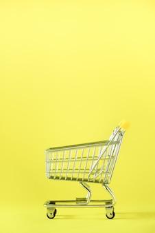 Carrello della spesa su sfondo giallo. carrello del negozio al supermercato. vendita, sconto, concetto di shopaholism. tendenza della società dei consumi