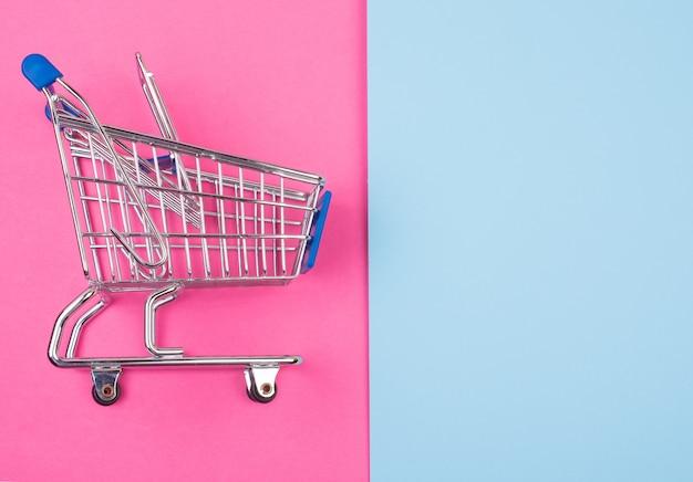 Carrello della spesa sul rosa e blu