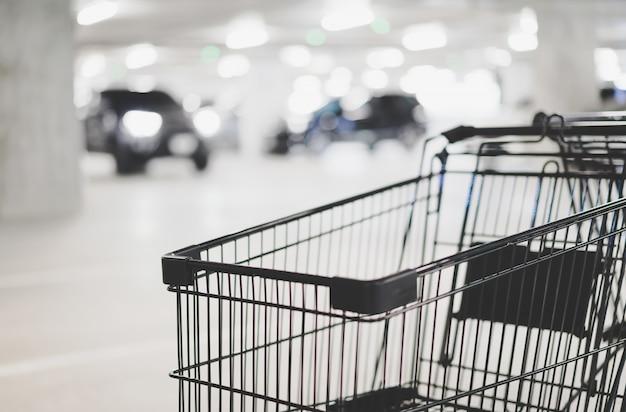 Carrello di acquisto vuoto ed automobile vaga al parcheggio, tono di colore di inverno
