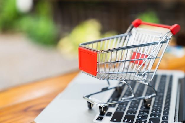 Carrello di acquisto vuoto sulla tabella con la tastiera del computer portatile e lo spazio della copia per il concetto online di acquisto