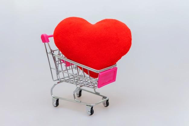 Carrello di spinta della drogheria del piccolo supermercato per acquisto e cuore isolato su bianco