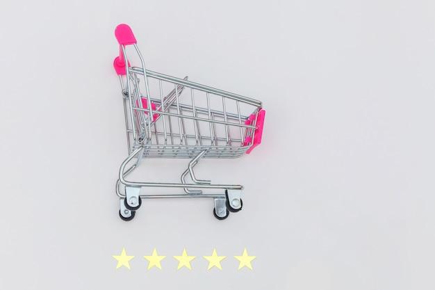 Carrello di spinta della piccola drogheria del supermercato per il giocattolo di compera con le ruote e una valutazione di 5 stelle isolata su fondo bianco. consumatore al dettaglio che acquista concetto online di valutazione e recensione.