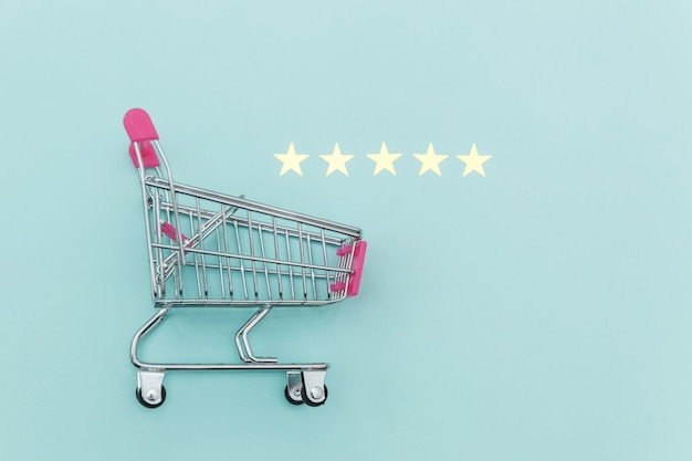Carrello di spinta della piccola drogheria del supermercato per il giocattolo di compera con le ruote e una valutazione di 5 stelle isolata su fondo blu pastello. consumatore al dettaglio che acquista concetto online di valutazione e recensione.
