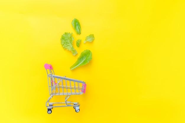 Carrello di spinta della piccola drogheria del supermercato per la compera con le foglie verdi della lattuga isolate su fondo d'avanguardia variopinto giallo
