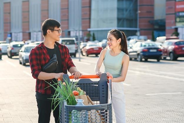 Carrello di trasporto sorridente del mercato del giovane ragazzo e ragazza vietnamiti con alimento differente vicino al supermercato