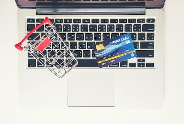 Carrello e carta di credito con il computer portatile sullo scrittorio