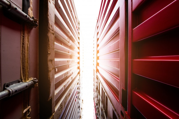 Carrello elevatore a forcale che solleva il contenitore di carico nell'iarda di spedizione o nell'iarda del bacino contro il cielo di alba con la pila del contenitore di carico nel fondo per l'importazione del trasporto, l'esportazione e il concetto industriale logistico