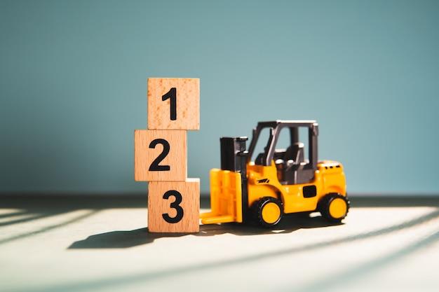 Carrello elevatore a forcale miniatura con il numero di blocco di legno usando come concetto della concorrenza di affari