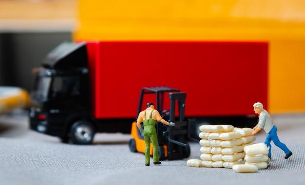Carrello elevatore dei lavoratori del magazzino che porta i sacchi al camion dei semi con il rimorchio