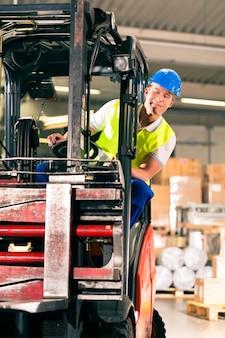 Carrello elevatore in giubbotto protettivo guida carrello elevatore presso il magazzino della società di spedizioni