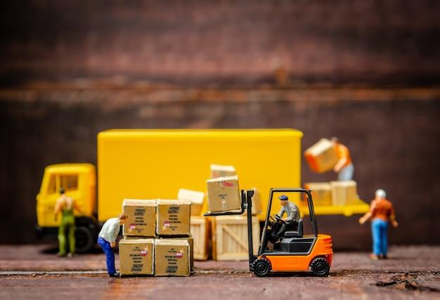 Carrello elevatore miniatura dei lavoratori del magazzino che porta il contenitore di merci al camion dei semi con il rimorchio