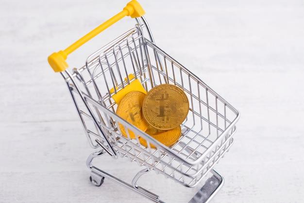 Carrello giallo con alcuni soldi di bitcoin, concetto online di compera