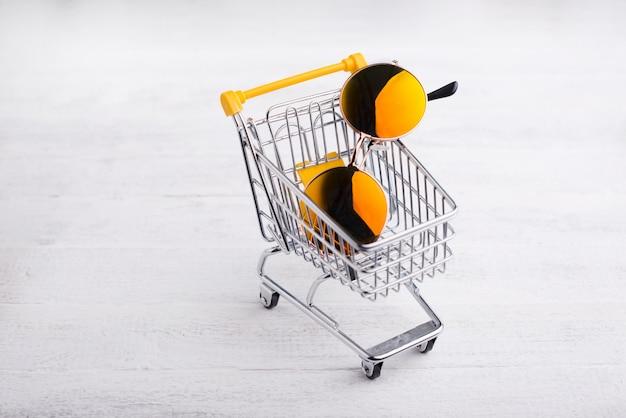 Carrello giallo con occhiali da sole rotondi hipster, concetto di shopping online