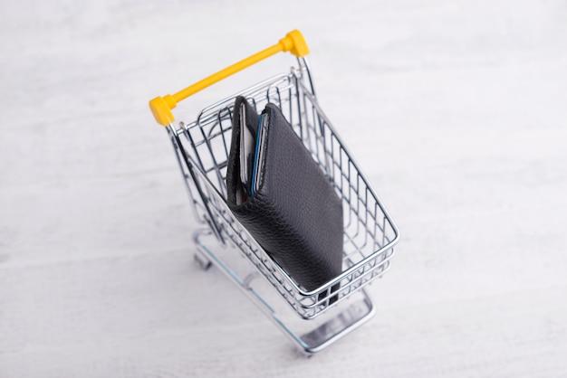 Carrello giallo con portafoglio nero, concetto online di compera