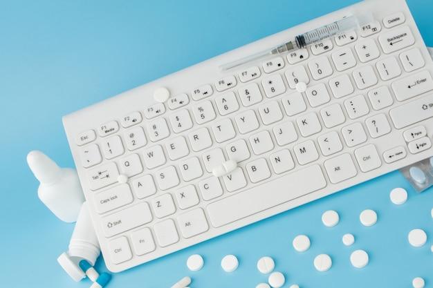 Carrello giocattolo con medicinali e tastiera. pillole, blister, bottiglie mediche, termometro, maschera protettiva su sfondo blu. assistenza sanitaria e acquisti su internet.