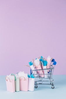 Carrello in miniatura pieno di sacchetti di carta