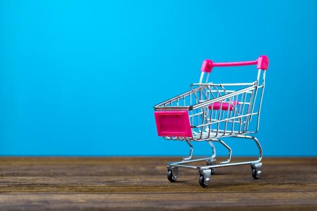 Carrello o carrello del supermercato su legno