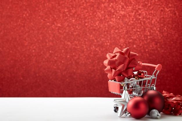 Carrello pieno di ornamenti natalizi su sfondo rosso