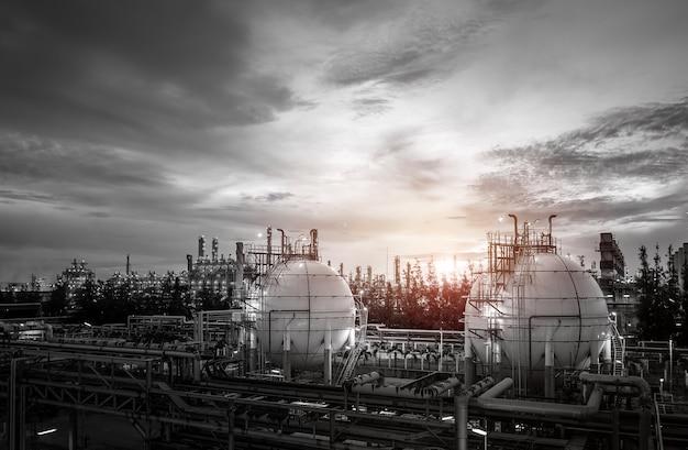 Carri armati e conduttura della sfera di stoccaggio del gas in impianto industriale della raffineria del gas e del petrolio sul tramonto del cielo