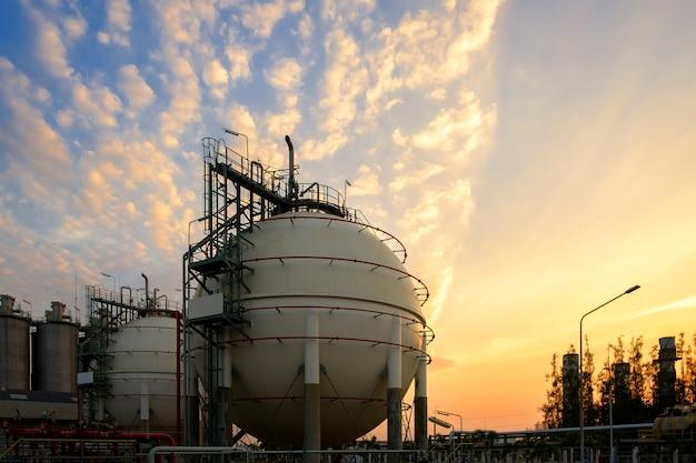Carri armati e conduttura della sfera di stoccaggio del gas in impianto industriale petrolchimico sul fondo di tramonto del cielo, fabbricazione dell'impianto di industria petrolifera