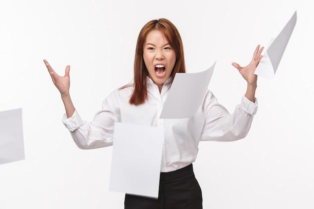 Carriera, vita in ufficio e concetto delle donne. ritratto di donna asiatica odiosa incazzata in camicia, arrabbiata con cattive scartoffie, lancio di carte, grida arrabbiate e smorfie odiose,