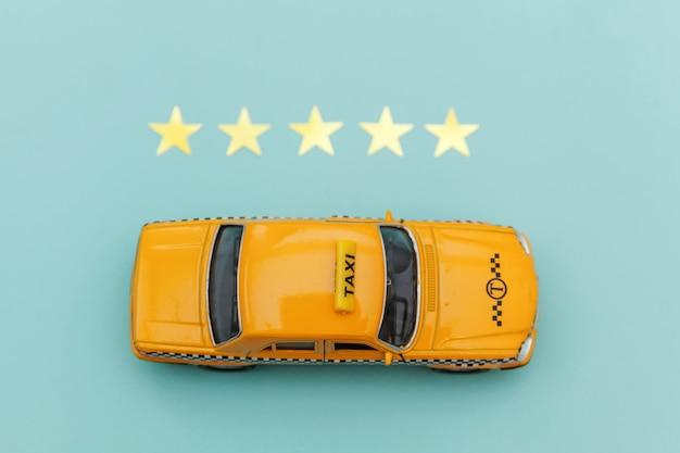 Carrozza di taxi gialla dell'automobile del giocattolo e una valutazione di 5 stelle isolata su fondo blu. applicazione del telefono del servizio taxi per la ricerca online di chiamata e prenotazione concetto di cabina. simbolo taxi. copia spazio.