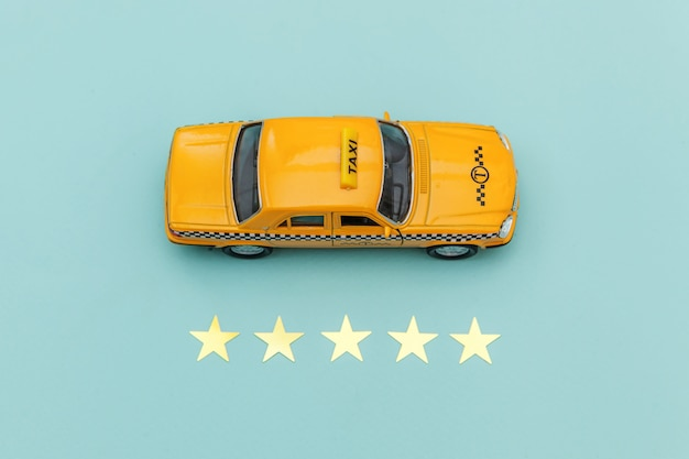 Carrozza di taxi gialla dell'automobile del giocattolo e una valutazione di 5 stelle isolata su fondo blu.
