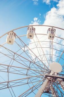 Carrozze di una ruota panoramica su uno sfondo di cielo blu