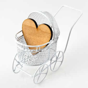 Carrozzina con cuore di legno su fondo bianco. biglietto di auguri neonato.