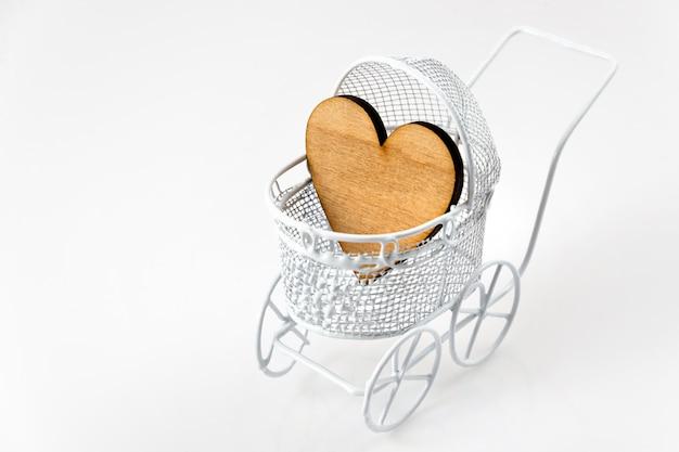 Carrozzina con cuore in legno su sfondo bianco con spazio di copia per il tuo messaggio. biglietto di auguri neonato.
