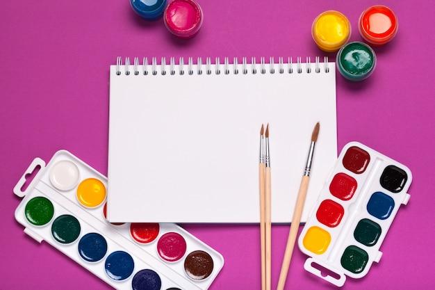 Carta, acquerelli, pennello e alcuni oggetti d'arte si chiudono sulla vista dall'alto
