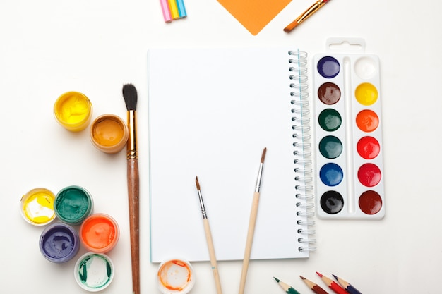 Carta, acquerelli, pennello e alcuni oggetti d'arte su una vista del piano del tavolo